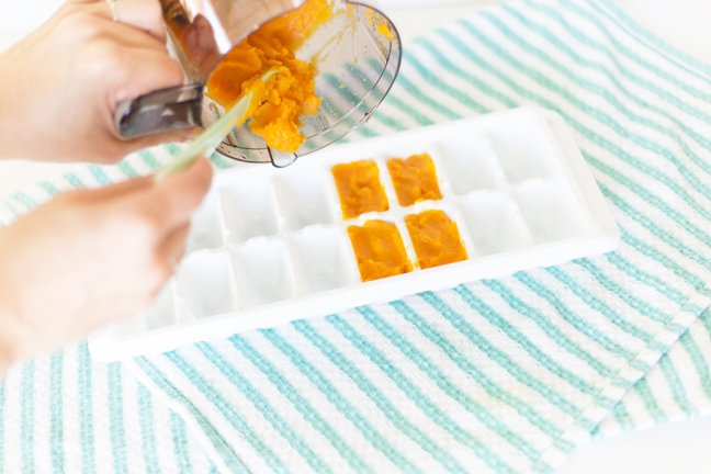 Pouring baby food in to the ice cube tray to freeze